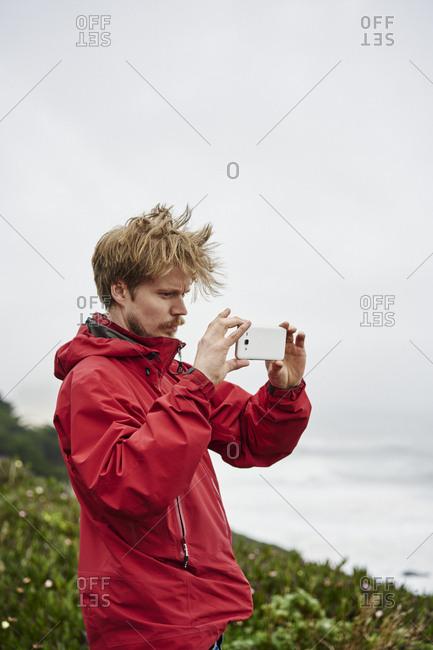 Man taking photograph at Big Sur in California, USA