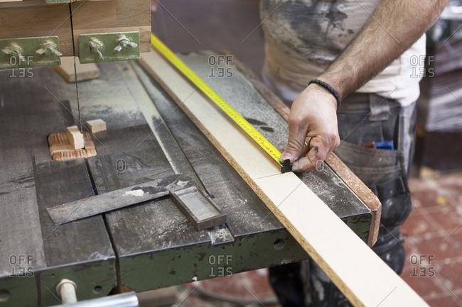 Carpenter measuring a length of wood in Sweden