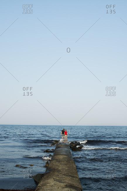 Teenage boys standing on a sea wall in Simrishamn, Sweden