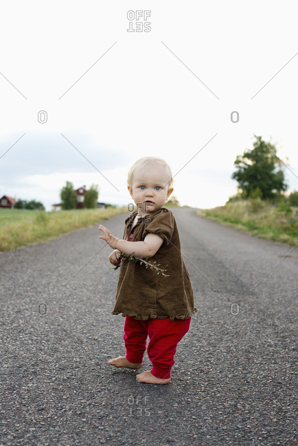 Baby girl standing on a rural road in Smaland, Sweden