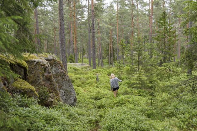 Woman walking through forest in Ostergotland, Sweden