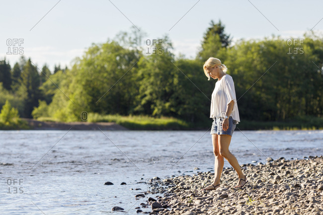 Woman on riverbank in Syssleback, Sweden