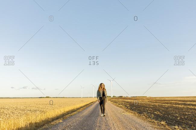 Teenage girl walking on rural road in Vaderstad, Sweden