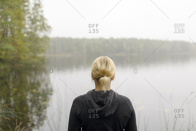 Blonde woman by lake in Ostergotland County, Sweden