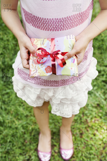 Girl holding present at birthday party