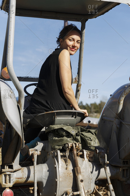 Mid adult woman on tractor in Sweden