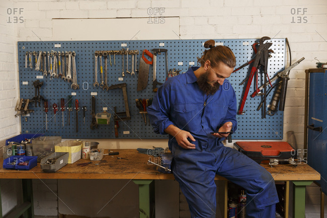 Mechanic checks his phone in a workshop in Sweden