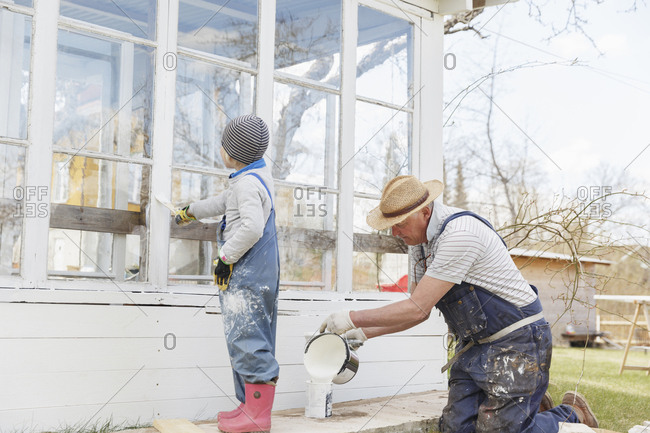 Grandfather and grandson painting building exterior in Sweden