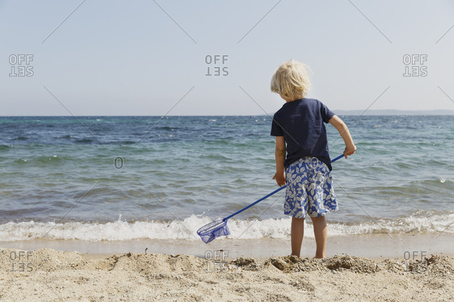 Boy holding a net in Les Issambres, France