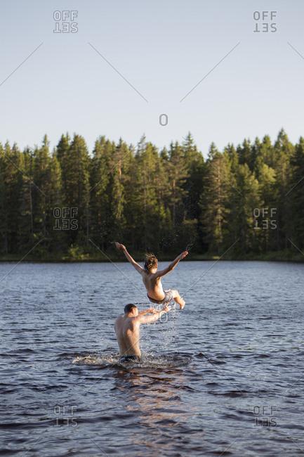 Man throwing a teenage boy in a lake in Kilsbergen, Sweden