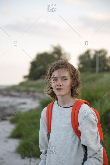 Teenage boy wearing a backpack on a beach in Osterlen, Sweden