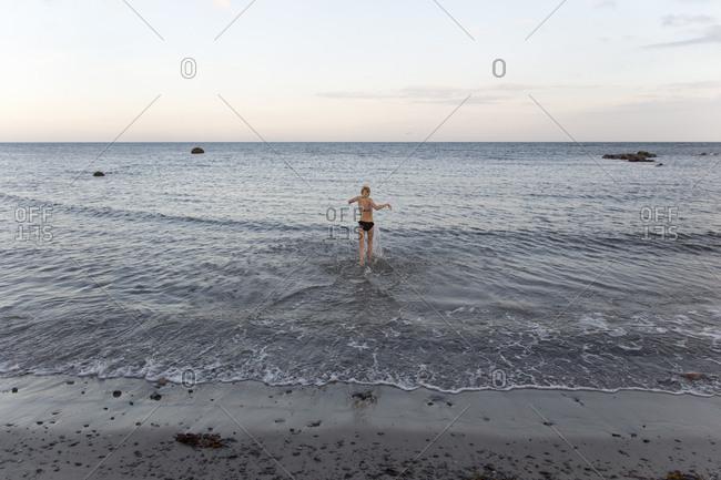 Girl in a bikini wadding in the sea in Ornahusen, Sweden