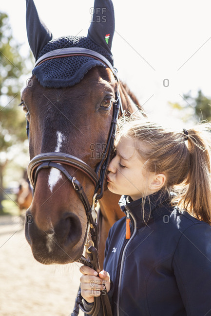 Teenage girl kissing a horse in Sweden