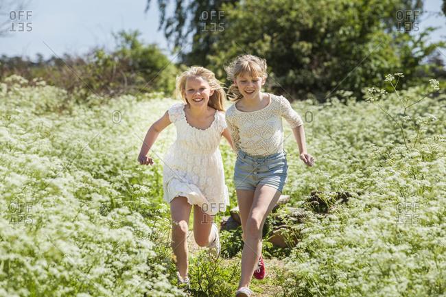 Two teenage girls running through field in Blekinge, Sweden