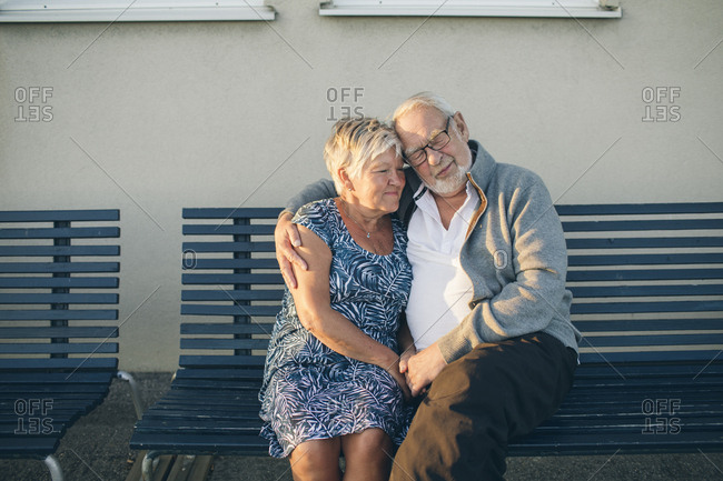 Senior couple hugging on bench