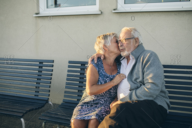 Senior couple kissing on bench