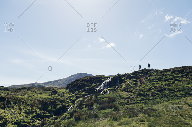 People hiking on hill on Isle of Skye, Scotland