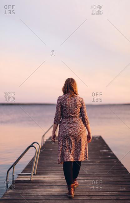 Rear view of woman on pier at beach in Blekinge, Sweden
