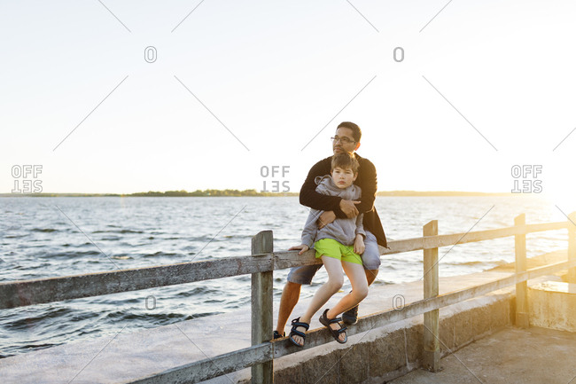 Father and son sitting on a pier at sunset in Blekinge, Sweden