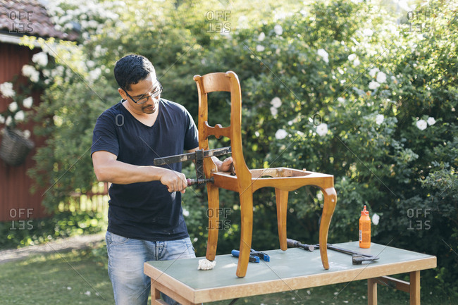 Mid adult man repairing a chair outdoors in Kvarnstugan, Sweden
