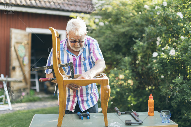 Senior man repairing a chair outdoors in Kvarnstugan, Sweden