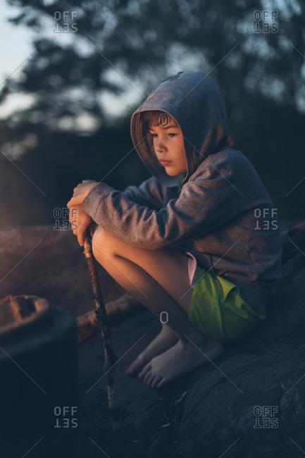 Boy sitting by campfire in Sweden