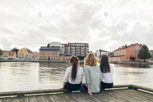 Three young women sitting on a pier in Karlskrona, Sweden