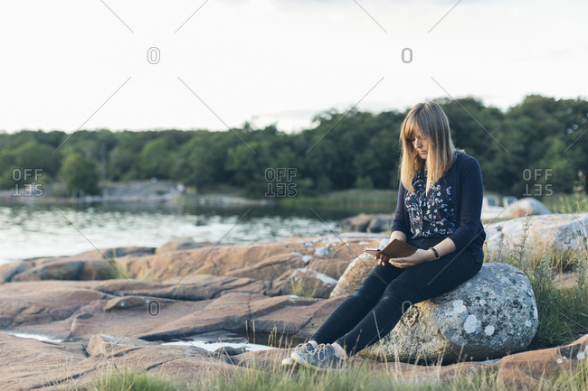 Mid adult woman reading outdoors in Karlskrona, Sweden