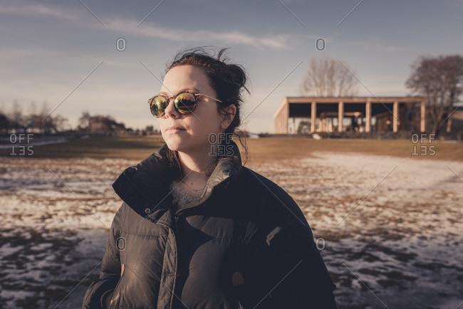 Woman wearing sunglasses during winter in Enskede, Sweden