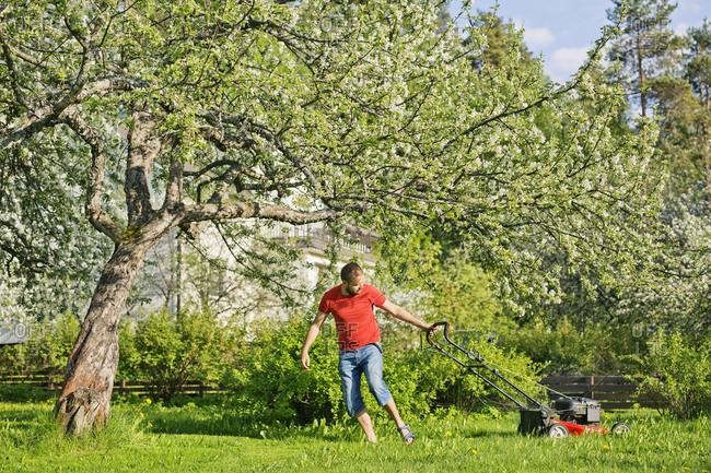 Mid adult man mowing lawn in Heinola, Finland