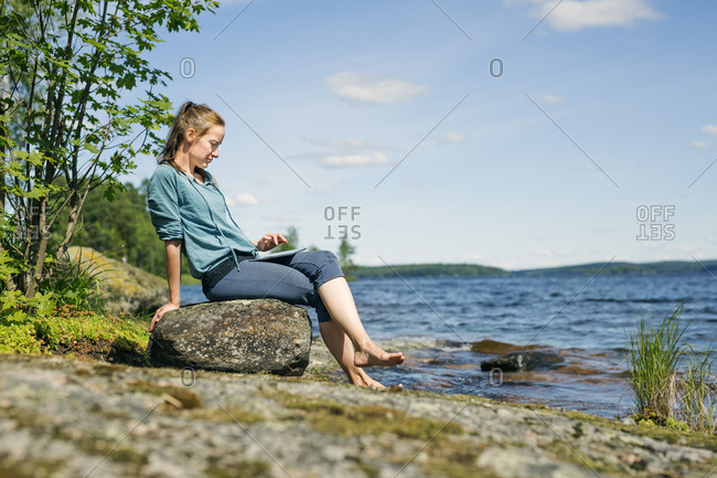 Mid adult woman looking at a tablet in front of a lake in Finland