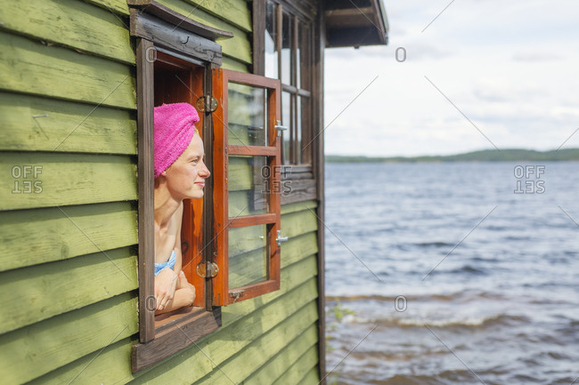 Mid adult woman looking out the window of a sauna in Finland