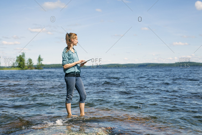 Mid adult woman holding a tablet standing in a lake in Finland