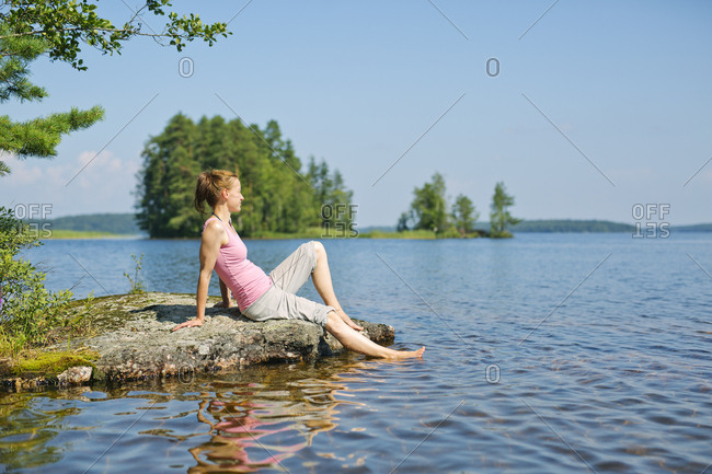 Mid adult woman sitting next to a lake in Finland