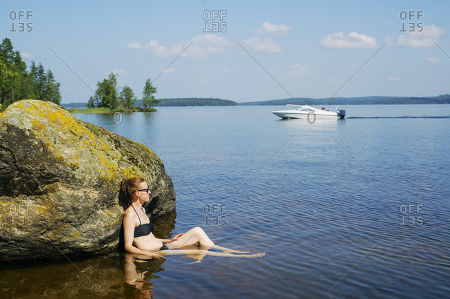 Mid adult woman sitting in a lake in Finland