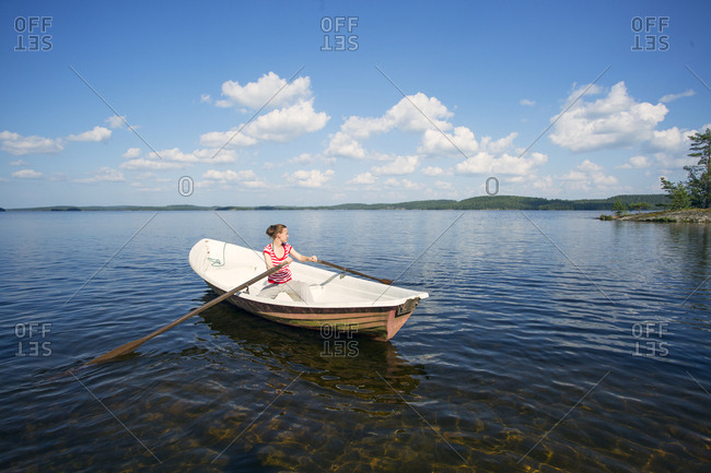Mid adult woman rowing a boat in a lake in Finland