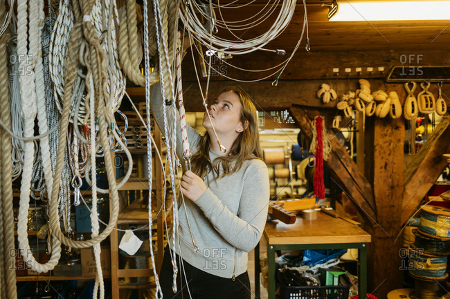Teenage girl reaching up to touch ropes in rope maker store