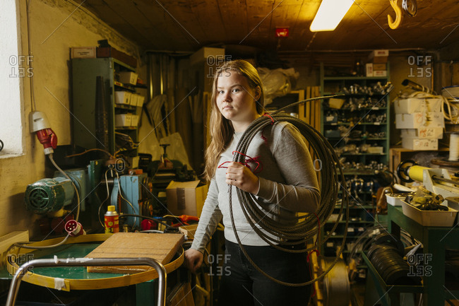 Teenage girl holding coil of rope in rope maker shop