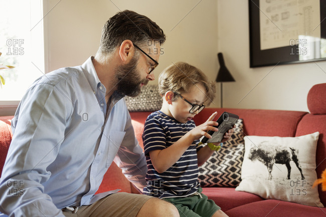 Mid Adult man and boy using a device in a living room in Sweden