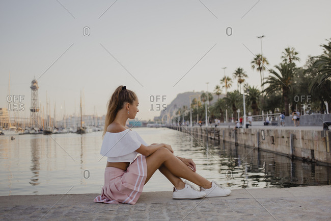 Fashionable young woman sitting at the harbor of Barcelona- Spain