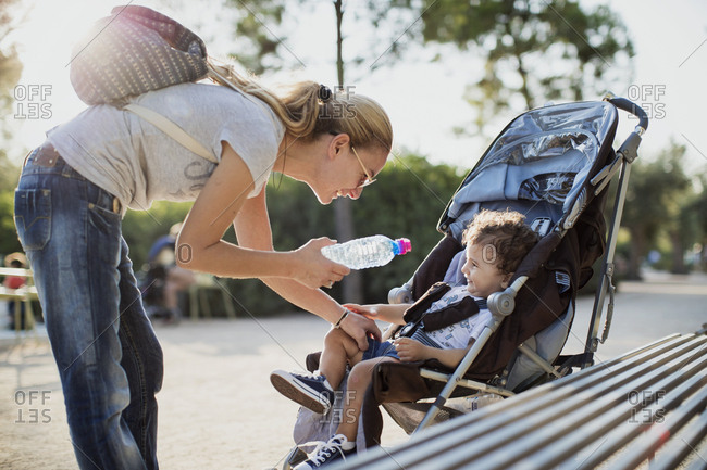 Mother giving water bottle to his son- sitting in pram