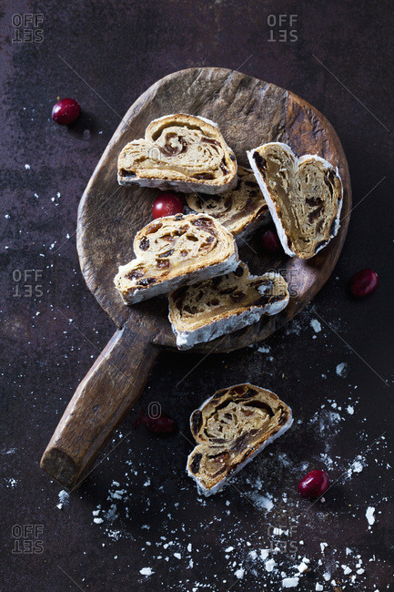 Sliced Christmas Stollen with icing sugar on a wooden scoop