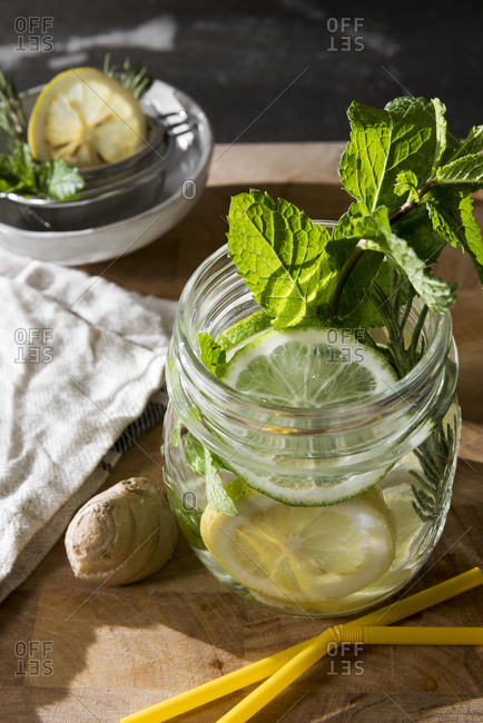 Glass of detox water with mint- ginger- rosemary and limes