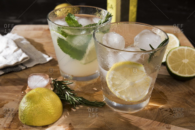 Glasses of Gin Tonic with lime- mint- rosemary and ice and with lemon- rosemary and ice