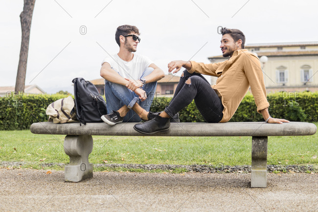 Young gay couple relaxing on bench