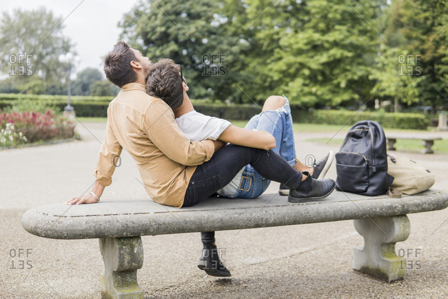 Young gay couple relaxing together on bench