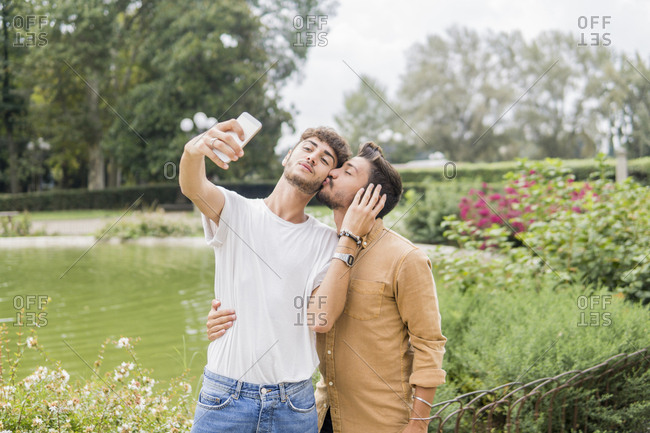 Young gay couple taking selfie with smartphone at city park