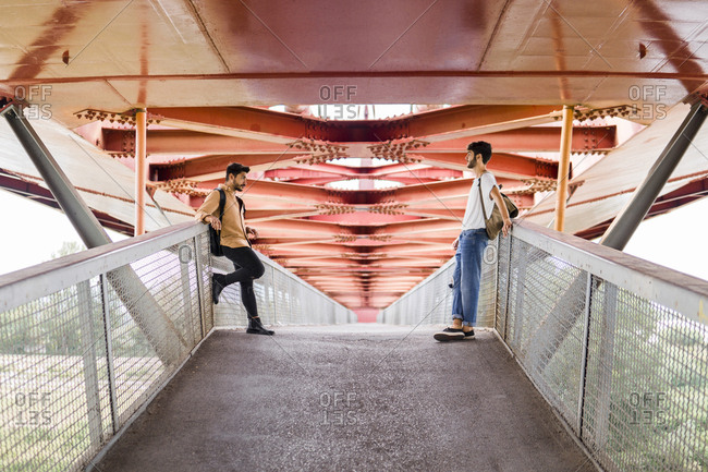 Young gay couple standing on modern footbridge looking at each other