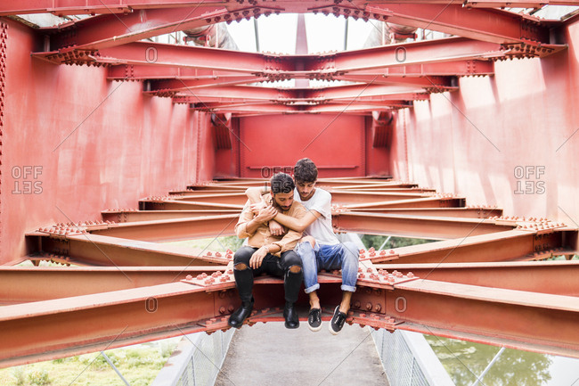 Young gay couple in love sitting on steel girder of a footbridge looking down
