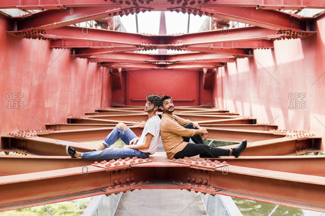 Young gay couple sitting back to back on steel girder of a footbridge